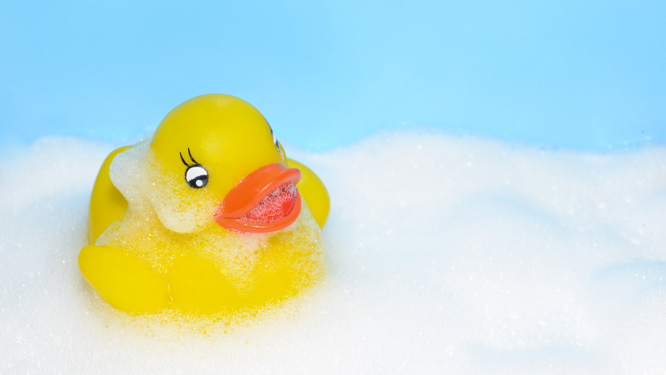 Yellow rubber duck covered in soap floating in a bathtub.